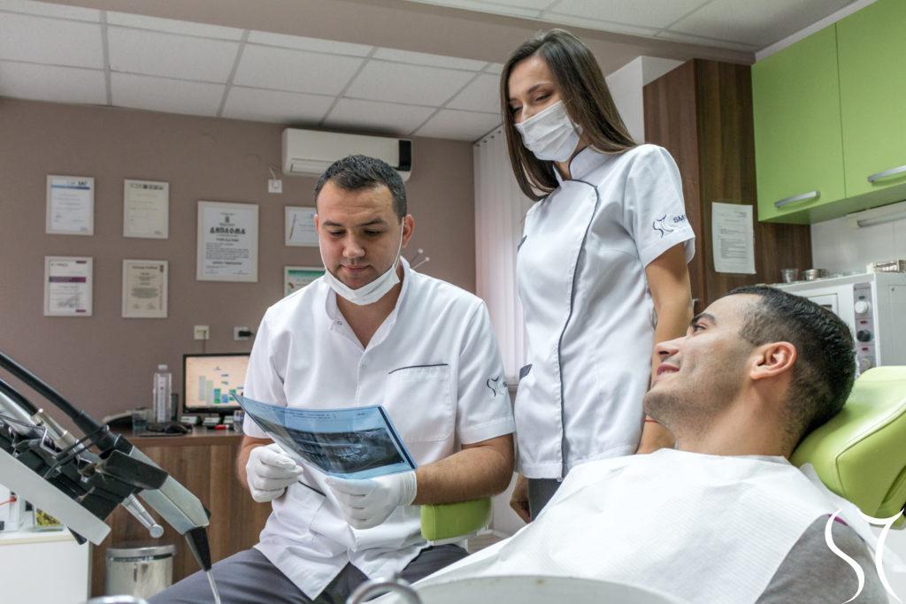 Doktori pokazuju pacijentu snimak zuba